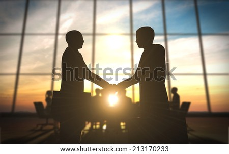 Two business shake hand in office silhouettes - stock photo
