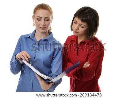 Two business woman chatting away together going over some notes - stock photo