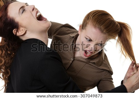 two business woman fighting each other at work  - stock photo