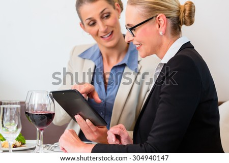 Two business women discussing presentation in restaurant having lunch - stock photo