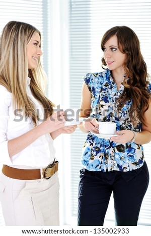 Two Business women enjoying a cup of coffee and smiling - stock photo