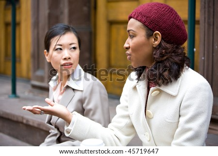 Two business women having a casual chat or discussion in the city perhaps on their lunch break. Shallow depth of field. - stock photo