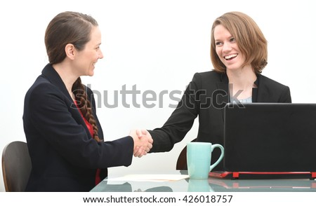 Two business women in job interview or making a negotiation shaking hands - stock photo