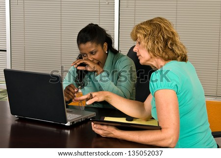 Two business women look at a laptop in an office conference room, one of the women yawns as if tired or bored with the work. - stock photo