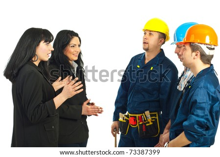 Two business women managers talking with team of constructor workers men isolated on white background - stock photo