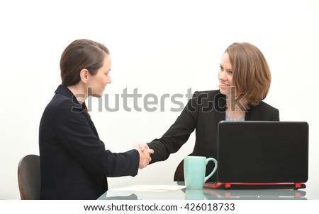 Two business women shaking hands in meeting or interview - stock photo