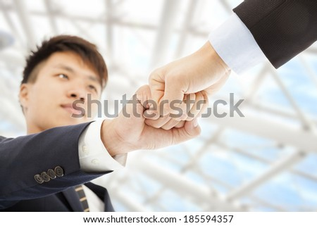 Two businessman fist  collide each other to celebrate - stock photo