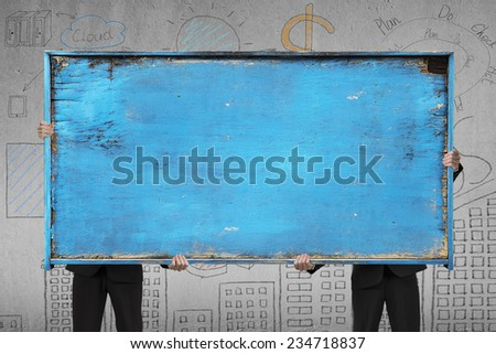 two businessman holding old blue blank wooden noticeboard on doodles wall background - stock photo