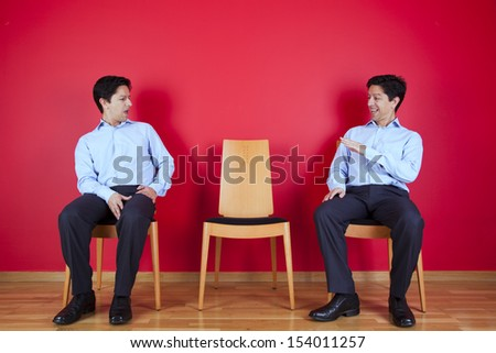 two businessman looking each other with a suspicion look, next to a red wall - stock photo
