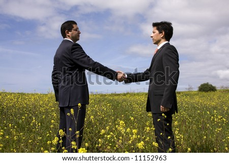 two businessman making a deal with a handshake at the field - stock photo
