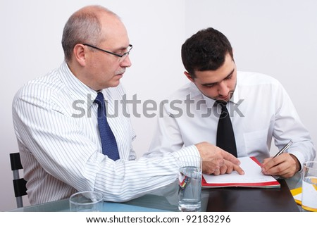 Two businessman, one mature and one young sitting at table during meeting - stock photo