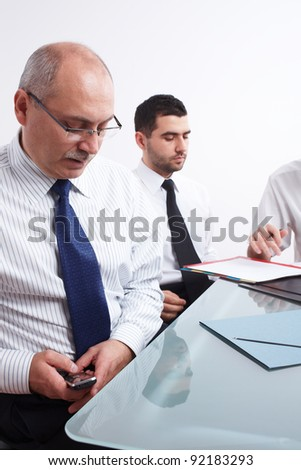 Two businessman, one mature texting using his mobile phone and one young sitting at table during meeting - stock photo