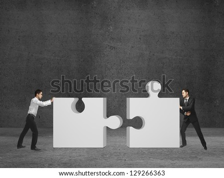 two businessman puts puzzle on room - stock photo
