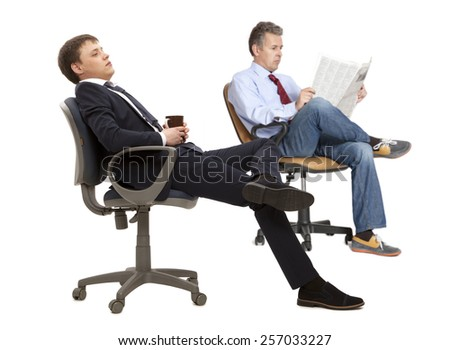 Two businessman resting in armchair with legs up isolated on white background - stock photo