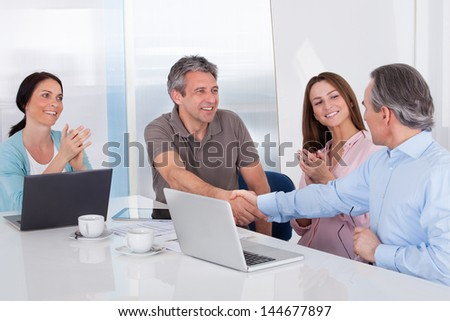 Two Businessman Shaking Hand In Front Of Colleague In Office - stock photo