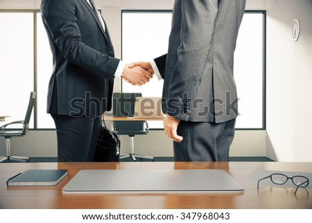 Two businessman shaking hands in a modern office - stock photo