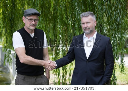 two businessman shaking hands outdoors in a park - stock photo