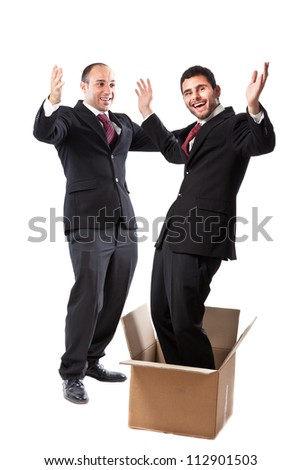 Two Businessman standing on a white background; one of them is popping out of a box - stock photo