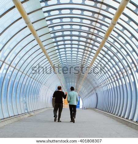 Two businessman walking in the modern tunnel. United Kingdom, London, Canary Wharf area.  - stock photo