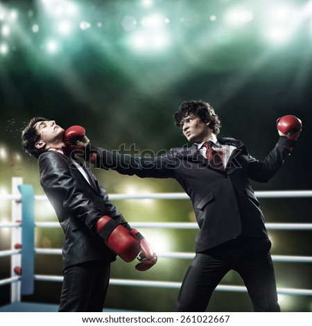 Two businessman with boxing gloves in the ring fighting with each other - stock photo