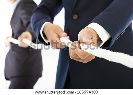 Two businessman work together and playing tug of war - stock photo