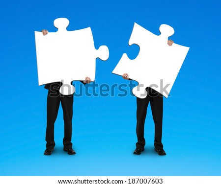 Two businessmen assembling puzzles blue background - stock photo