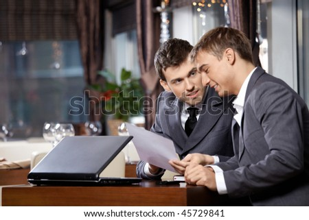 Two businessmen at restaurant discuss the document - stock photo