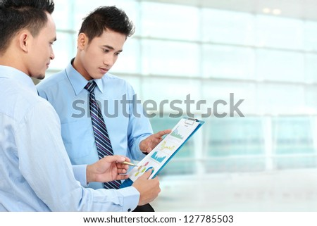 Two businessmen discussing a business chart growth in the office - stock photo