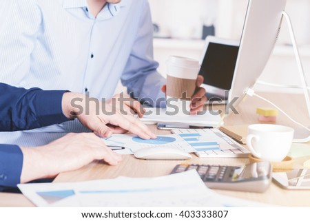 Two businessmen discussing business chart over coffee in office - stock photo