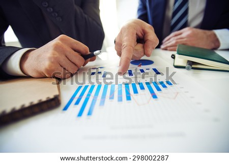 Two businessmen discussing chart while one of them pointing at it - stock photo