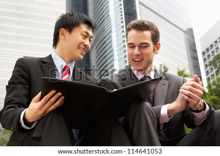 Two Businessmen Discussing Document Outside Office - stock photo