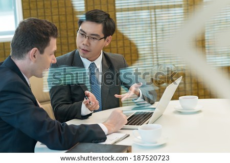 Two businessmen discussing something during coffee break - stock photo