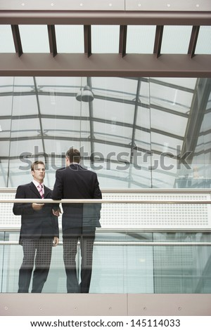 Two businessmen discussing while standing against glass railing in office - stock photo