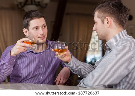 Two businessmen drinking together cognac after work - stock photo