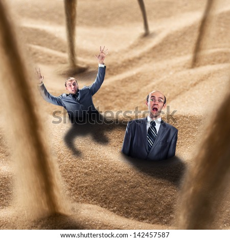 Two businessmen fall into the quicksand trap - stock photo
