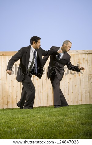Two businessmen fighting on lawn - stock photo