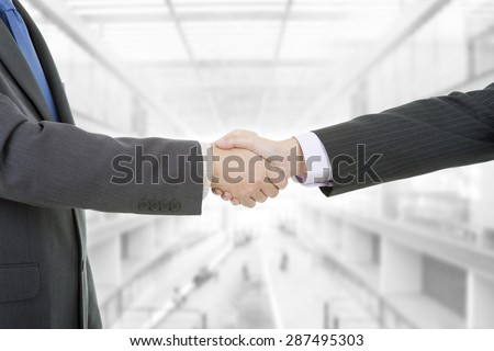 Two businessmen handshake at the office - stock photo