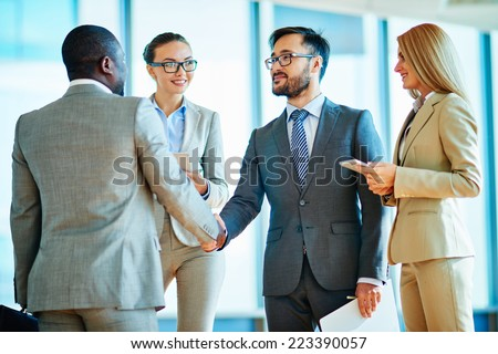 Two businessmen handshaking after signing contract with their female colleagues near by - stock photo