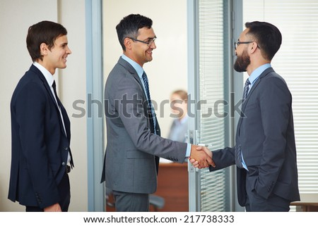 Two businessmen handshaking in office after signing contract - stock photo