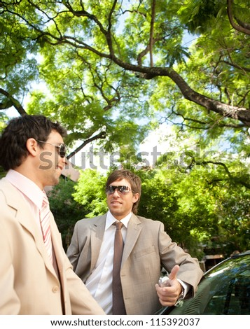 Two businessmen having a conversation while leaning on a car in a tree lined street in the city. - stock photo