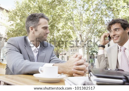 Two businessmen having a meeting in a coffee shop's terrace in the city, outdoors. - stock photo