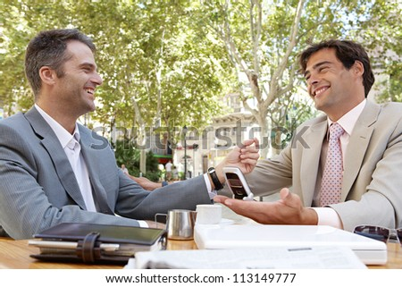Two businessmen having a meeting in a coffee shop terrace outdoors. - stock photo