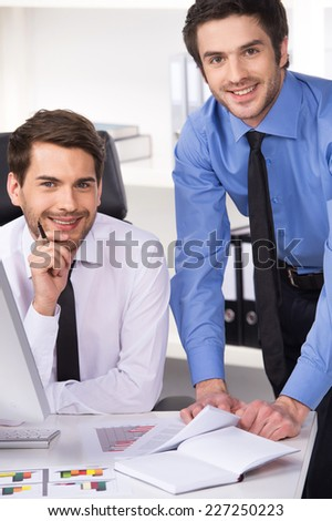 two businessmen having discussion in office. Two businessmen looking at camera and graphs on table - stock photo