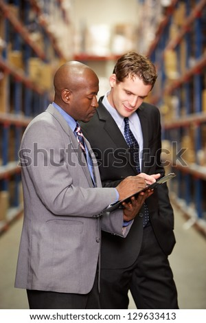 Two Businessmen Having Discussion In Warehouse - stock photo