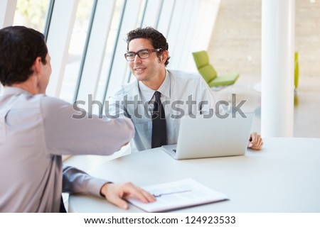 Two Businessmen Having Meeting Around Table In Modern Office - stock photo
