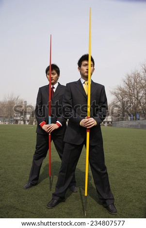 Two Businessmen Holding Javelins - stock photo