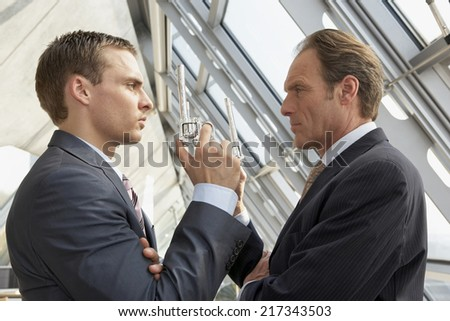 Two businessmen holding revolvers and looking at each other - stock photo