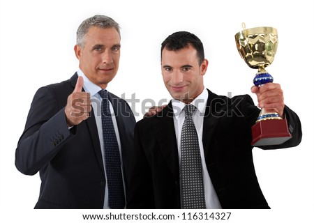 Two businessmen holding trophy - stock photo