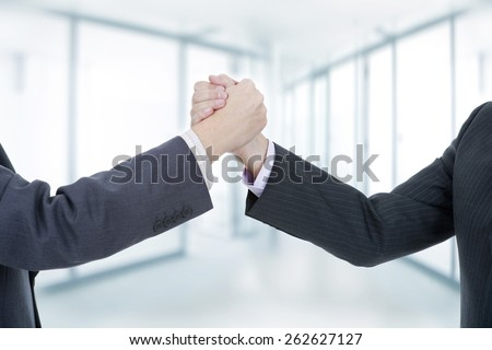 two businessmen in a handshake, at the office - stock photo