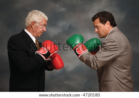 Two businessmen in business suites facing off with boxing gloves - stock photo